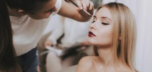 Woman adding makeup to a client
